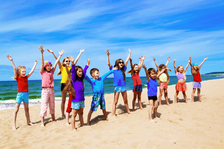 Active Sporty Children Doing Exercise On The Beach